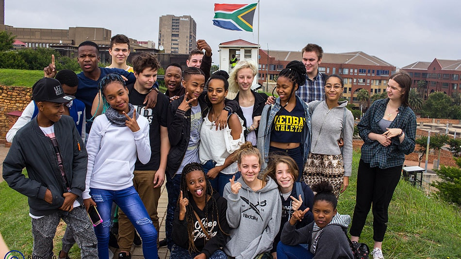 Photo of a participating youth group standing in a field. There are buildings and a South African flag on a flagpole in the background.