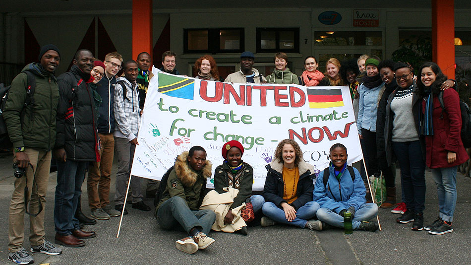 "Photo of a group of participants in front of a building. They are holding a poster with the slogan ""United to create a climate for change now""."