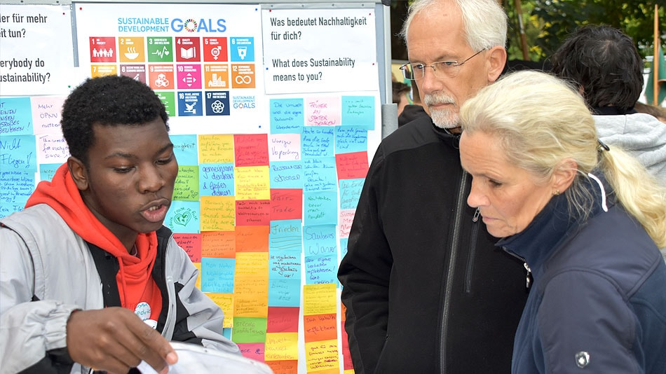 "A participant is standing at an exhibition stand, explaining something to a man and a woman. There are posters hanging in the background, showing the development goals and the question, ""What does sustainability mean to you?"""