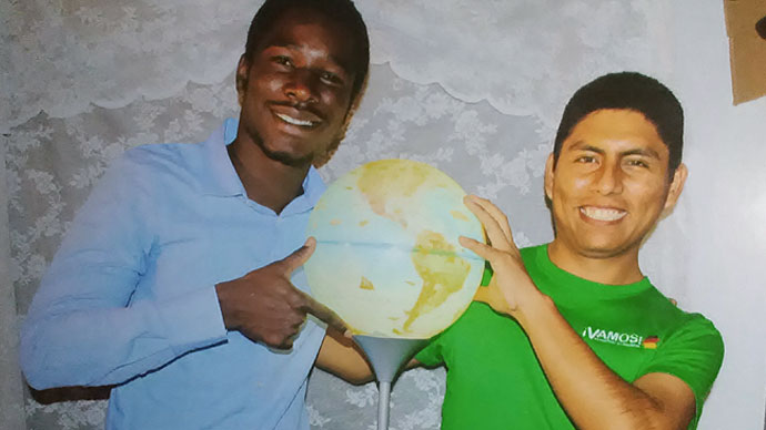 Arturo with a friend. Between them they are holding a lamp in the shape of a globe.