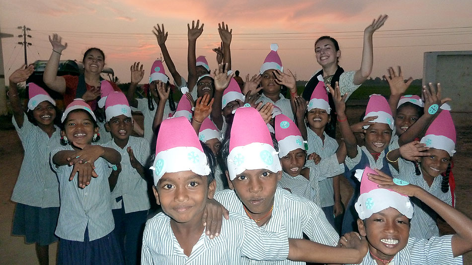 A group of children wearing santa hats. Two volunteers are standing in the background.