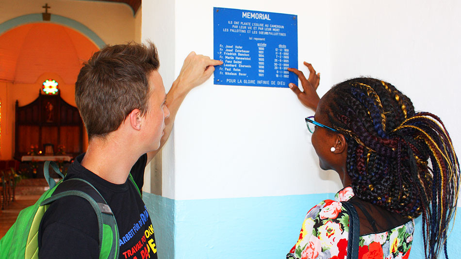 Two young people in front of a commemorative plaque, both pointing at the plaque.