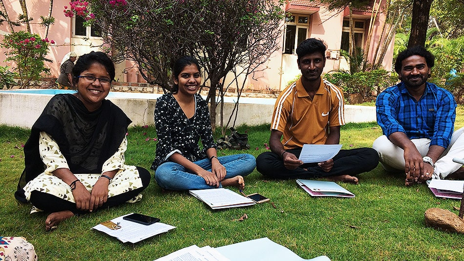 Four volunteers sitting cross-legged on a lawn. In front of them are pieces of paper with words written on them.