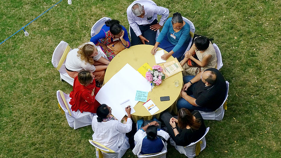 An overhead view of a round table, at which a group is working on some documents together.