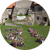 Conference participants sit on the lawn in front of an old wall. They are seated in the shape of a question and exclamation mark.