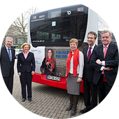 The management team of Engagement Global, the BMZ and the then Minister for Federal Affairs, Europe and Media of the state of North Rhein-Westphalia, Angelica Schwall-Düren, in front of a bus featuring an Engagement Global advert.