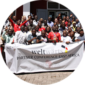 "Group photo from the weltwärts partner conference featuring a banner with the words ""weltwärts partner conference East Africa""."